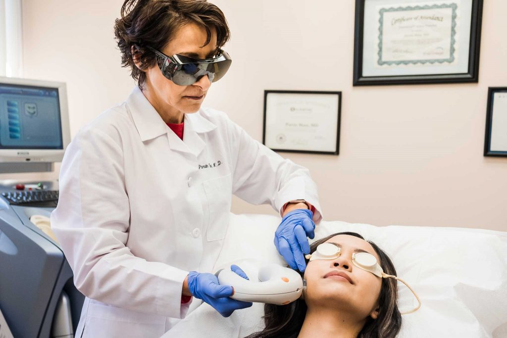 Dr. Mani performing cosmetic procedure on woman's cheek